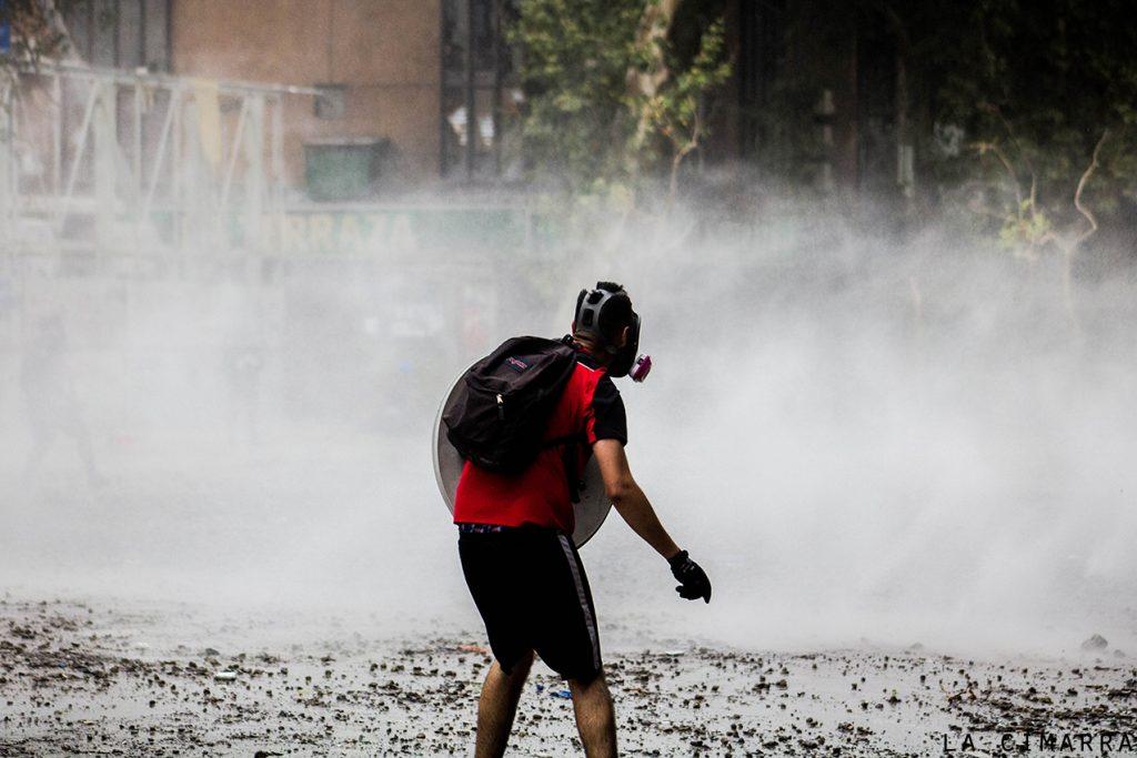 Hombre capucha defendiendo la primera línea en plaza Dignidad, Santiago de Chile