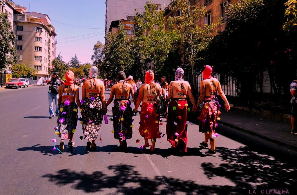 Mujeres marchando con el nro de femicidios por año en Chile, en dirección a la alameda en santiago de Chile
